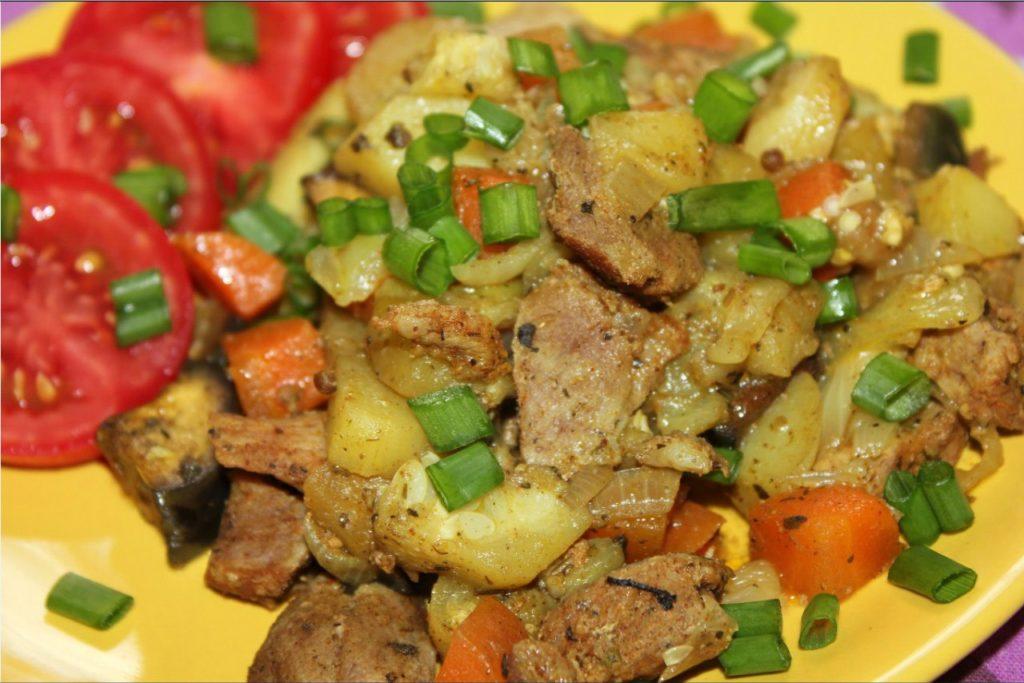 Свинина с овощами томат зеленый лук на тарелке
