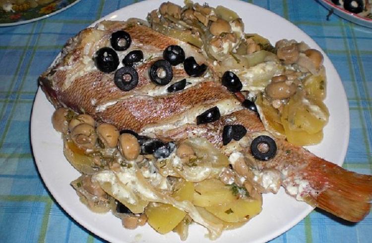 Готовый окунь с картофелем, маслинами и грибами